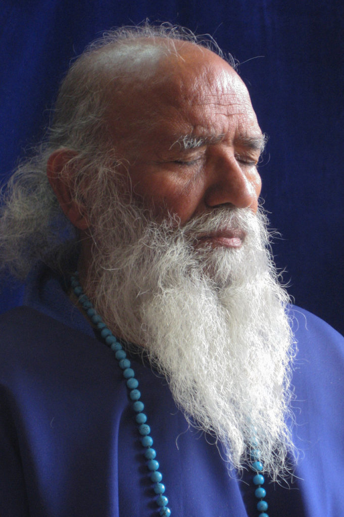Swami Shyam wearing a silk purple poncho in profile meditating